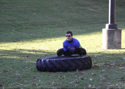 white man flipping tractor tire
