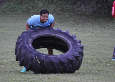 black man flipping tractor tire